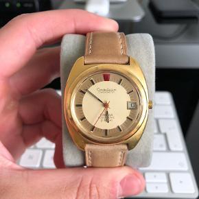 """Her sælges et Omega F300 Constellation Chronometer Urværk: Cal. 1250 Quartz Referencenummer: 198.002 Årgang: 1972 Størrelse: 39 mm. med krone, 37 mm. uden krone. Stand: 8,5/10 - nærmest helt perfekt stand, og uret har fået nyt batteri for 2 måneder siden, så det går fuldstændig perfekt, både tid og datoskift. Uret sælges som """"watch only"""" med et ægthedsbevis og 2 urremme."""