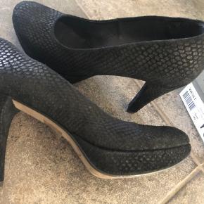 Smukke heels i sort med slangeskind struktur i ruskind. Er brugt en gang og er som nye. Er behagelige at have på. Hælen måler 10,5 cm. Plateau foran er 2 cm. Nypris 1100,-