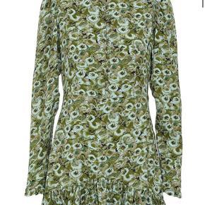 Gudeskøn By Numbers silkekjole med smukke detaljer fra custommade. Kjolen har høj krave, krystal knapper ned foran og lange ærmer. Den kommer i en tung silkekvalitet med blomsterprint og med flæser i bunden og ved ærmets ende.  Materiale: 100% silke Pasform: Normal  Str. 36 / S