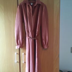 Flot vintage - retro kjole. Str M. Kjolen er i rigtig god stand. Fint bælte og lette skulderpuder. Stoffet er let skinnende. Mål: længde: 107 cm, talje: 2*41, bryst: 2*45 cm.
