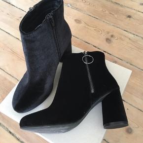 """Sælger mine flotte støvler fra Bianco i str. 38. De er i sort velour og har den fineste runde sål. De lukkes med lynlås på """"indersiden"""" og har en pyntelynlås på ydersiden. Hælen er ca. 8,5 cm høj.  Har aldrig fået dem på da jeg desværre måtte sande at de var for smalle til mine brede fødder. Så de er ALDRIG brugt :)  Originalprisen var 550. Har tilladt mig kun at slå lidt af prisen da de som nævnt aldrig er brugt og derfor fremstår helt som nye og uden slid eller mærker af nogen art."""