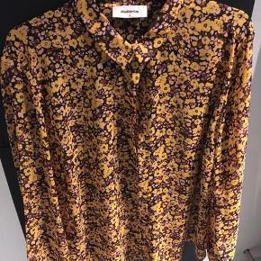 Sød blomstret skjorte fra Modstrøm  Uden fejl eller mangler,  med knaplukning fortil , lidt retro farver i gul, lyserød og brun.