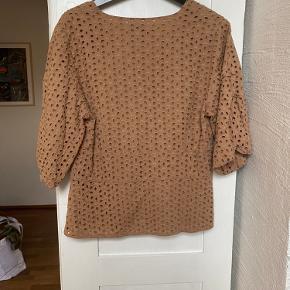 Lys brun farve med fint hulmønster, og lidt pufærmer.