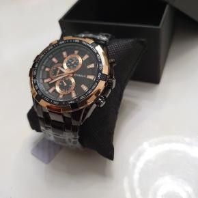 Armbåndsur CURREN Pris : 250 kr  Et spændende herreur fra Curren skabt i det kendte flotte design. Stålremmen er er sort og og matcher den sorte urskive i den forgyldte urkasse. Dette er et perfekt ur fra Curren til ham, der ønsker specielt unikt ur. De små urskiver og indstillingsknapperne er til pynt.  1 x armbåndsur ( Lækkert og stilfuldt CURREN herreur sælges nyt. Uret er udstyret med Quartz urværk, hvilket man bruger i mange kendte urbrands. Længde 23 cm justerbar urrem, urkasse diameter: 4.5 cm Materiale: Rustfrit stål,Vandtæt:3 ATM) 1 × gaveæske