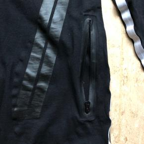 Celebratory limiter langærmet t-shirt fra HAN Kjøbenhavn i forbindelse med deres åbning af deres flagship i New York.  Lommer på front i begge sider Hvid stribe ned af ærme og side af krop Bagpå samme print som foran