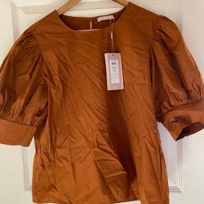 Skøn bluse fra PIECES af organic cotton i den smukkeste efterårsfarve. Blusen har korte ærmer og har en lille knap bagpå.