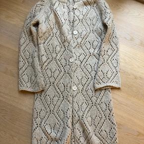 Smuk kidmohair/uld cardigan med guldtråde. Har lidt fnuller, derfor prisen.  Blød strik, brugt og har en lille misfarvning ved ærmerne, se fotos.   Længde 101 cm  Jeg er 177 cm (for at give indtryk af længden)