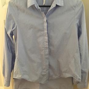 Vasket men ubrugt, desværre købt for lille. A-form og længere bagtil. Model Azzurro. Lys blå.