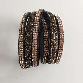 Super fint armbånd i sort med brunlige sten. Brugt 2 gange er som ny.