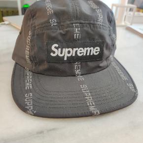Supreme 18FW relflective text stripe camp cap i sort. Købt i Supreme-butikken i Paris. På StockX står den til $ 95. Køb den her for kun 500 i en hurtig handel.