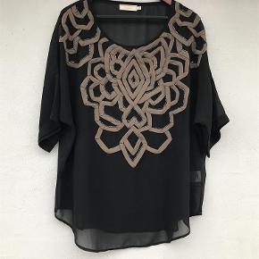 """Varetype: Sød transparant bluse Farve: Sort Oprindelig købspris: 399 kr.  Fin bluse med applikationer og perler.  100% polyester. Brystvidde: 2x67 cm. Længde 70 cm.   TRYK PÅ """"KØB NU"""" FOR AT SIKRE DIG HANDLEN :-)"""