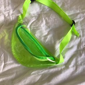 Neon grøn transparent bæltetaske. Der er 3 rum i tasken