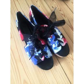 Blomstrede sandaler med plateau hæl og brede snørebånd. Helt almindelig i størrelsen. Sender gerne med DAO :)