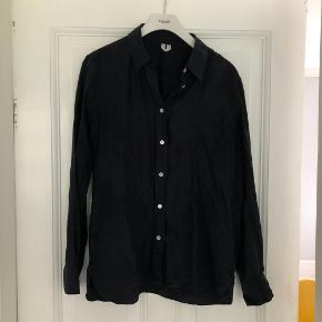 """Meget mørkeblå (næsten sort) skjorte i 100 % silke. Passer en str 38. En del """"lysere""""/""""hvidere"""" streger rundt om omkring (billede 2 og 3 illustrerer det). Ikke noget jeg selv bemærker, men det skal nævnes. Ved ikke om det bliver mindre synligt af at blive strøget - har ikke selv forsøgt."""