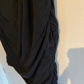 """Sort viskose nederdel i tykkere kvalitet. Perfekt til julefrokoster eller arrangementer i vintermånederne. Har """"folde"""" detaljer i siderne og foran"""
