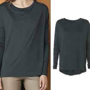 """Let og smart t-shirt fra By Malene Birger i en flot grøn farve og lavet i en skøn stretch kvalitet med lange ærmer. Materiale: 95% Viskose, 5% Elastan. Stylen hedder """"Maidali"""". Mener BMB kalder farven for """"exotic green"""". Det er en str L og den passer en str 42/44. Den har tætsiddende ærmer og er så ellers mere """"loose"""" - se billeder. Den kostede 600 kr og er kun brugt en enkelt gang i et par timer. Har ingen slidtage. Prismærke haves stadig. Sælges 250 kr + porto.  Handler helst via mobilepay - ønskes køb: oplys blot mobilnr og jeg anmoder om beløbet for varen + porto."""