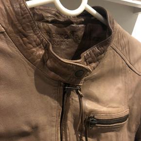 Lækker skindjakke i flot mellemrum farve - brugt men uden pletter, huller eller tegn på slidtage, kun en let patina som kun klæder jakken. Jakken har et let bomuldsfoer.