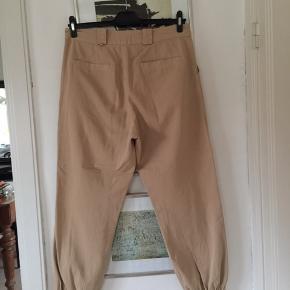 Beige cargo bukser med elastik ved fod. Str 42. Brugt en gang. Pris 100,- pp Bytter ikke.