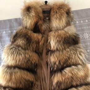 Meget lækker vaskebjørn pels vest i brune nuancer Sælges for 2800 kr  Ny pris 6000 kr   Ingen skam bud, tak!!!