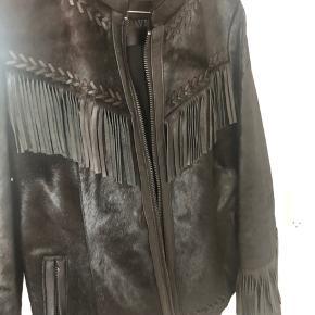 Smukkeste sorte jakke fra Ravn i skind med frynsedetaljer. Størrelse 36. Står som ny og brugt få gange.   Har aldrig været i butikkerne og havde en salgspris på omkring 10.000 kroner.   Sælges kun da jeg desværre ikke får den brugt nok.   Byd gerne. Skambud ignoreres.  Køber betaler fragt eller kan afhentes på Nørrebro.