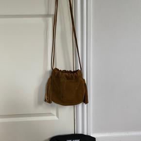 YSL Hobo taske i cinnamon farvet ruskind. Med to dekorative ruskindskvaste og et guldfarvet YSL monogram charm. Tasken kan bruges både som skulder og crossbody taske. Dustbag følger med. Måler 19x20x6 cm.