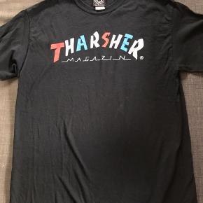 Supercool t-shirt fra Thrasher i sort med rød/hvid/blå skrift. I god stand uden huller. Str. M og brugt af dreng på 180 cm. Denne t-shirt er IKKE fake☺️det er meningen, at mærket/trykket er sådan. Se billede 2 for trykket i nakken.