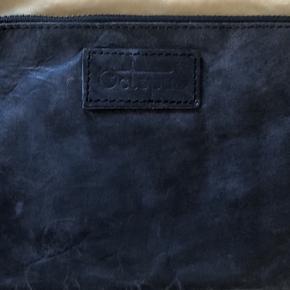 Håndtaske i mørkegrå med lille lomme med lynlås indvendig samt kortholder plads. Afhentes i Aarhus