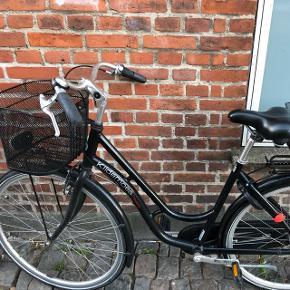 Sort Kildemoes damecykel med to kurve. Er købt af ældre dame, som bare har haft den stående i en kælder. Jeg har brugt cyklen i et halvt årstid og den virker upåklageligt. Ringeklokke er i stykker og lys mangler batterier, men de virker. Byd gerne.
