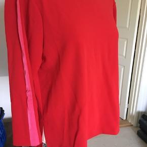 Rød med lysere rød stribe på ærmet - lidt længere bagpå.