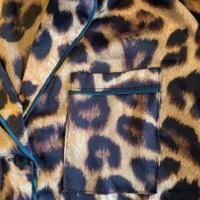 Neo Noir skjorte med leo-print, mørkegrønne detaljer, knapper og en brystlomme i Venstre side.  100% polyester.