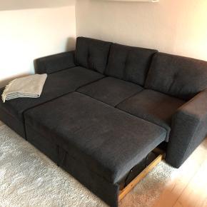 Lækker mørkegrå sovesofa med chaiselong. Rigtig god kvalitets sofa. 2,5 år gammel. Fremstår som ny. Ingen slid, pletter eller lignende. Er ikke fra et rygerhjem. Sælger sofa grundet flytning. Chaiselongen kan åbnes, hvor der er et rum til bl.a. dyne og pude, hvis man har overnattende gæster.  Skal afhentes af køber.   Mål samlet:  Bredde = 243 cm  Højde = 86 cm  Dybde = 89/163