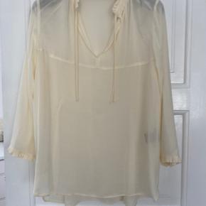 Bluse/tunika fra Stella Nova i cremefarve Cool løstsiddende skjorte med 3/4-lange ærmer og flæsedetaljer. Skjorten har en v-udskæring foran med bindebånd i løbegang. Købt 2019 Brugt meget få gange