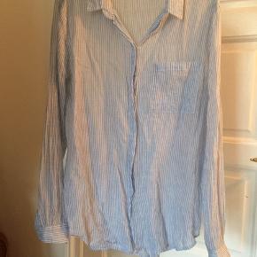 Fin let skjorte. Stribet hvid og lyseblå. Lomme på brystet. Let gennemsigtig. Nålestribet.