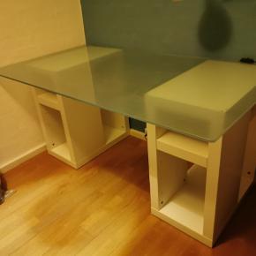 Skrivebord sælges Brugt i mange år, men med få brugsskader (kan sende billeder efter anmodning) Det består af 3 dele, 2 hylder i hvid Melamin og én glasplade Glaspladen er 180x80x1 Hylderne er begge 35x58x70 Nypris ukendt, sælger for 700, men er åben for bud