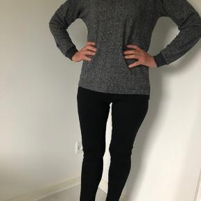 Smart gråmeleret bluse med lange ærmer fra Black Swan.  På ryggen står der '13' i skinnende sorte similisten.  Lille slids i siden på begge sider.  Mørkegråt ribstrykke ved ærmer og halsen.  Længde fra skulder er 58 cm, og brystmålet er 104 cm.  Fremstillet af 80% bomuld og 20% polyester.  Bærer ikke præg af brug.