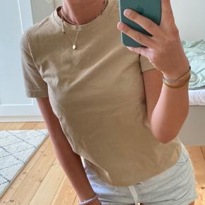 Gina Tricot basic t-shirt i sandfarvet str. XS. Den er gået med 1-2 gange, så standen er næsten som ny.  Ingen slitage.