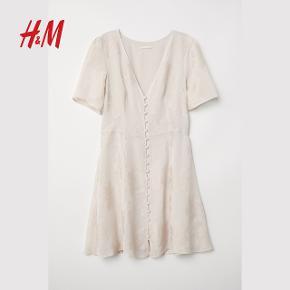 Konfirmationskjole, H&M Trend, str. findes i flere str., Beige/hvid, Ubrugt Sommerkjole. Kort kjole i let, jacquardvævet kvalitet med V-udskæring og korte pufærmer. Kjolen lukkes foran med beklædte knapper og er skåret i taljen med let vidde i underdelen. Med for. Meget yndig og feminin kjole. Helt ny og ubrugt med mærkeseddel. Materiale: 75% viscose og 25% polyester. For: 100% viscose. Nypris: 449 Eventuel fragt lægges oveni: 40 kr. til nærmeste posthus/butik Jeg har kjolen i str. 36, 38 og 44. Alle helt nye og ubrugte med mærkesedler