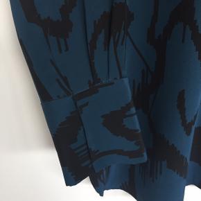 Smuk skjorte, der kun er brugt få gange, og fremtræder mæsten som ny. Skjorten har høj krave, og skjulte knaplukning og er i 100 % silke. Modelle hedder Alya.