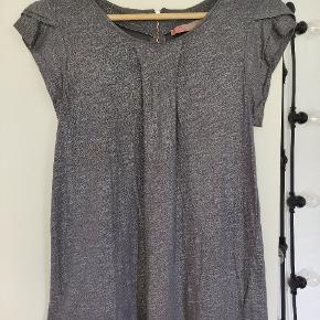 Fin sølvglimmer-bluse fra Saint Tropez. Fold i stoffet på midten af blusen og på ærmerne. Lynlås i nakken.  Syning i den ene side har drejet sig en smule (se billede). Det er en str. S, men svarer til en str. M.