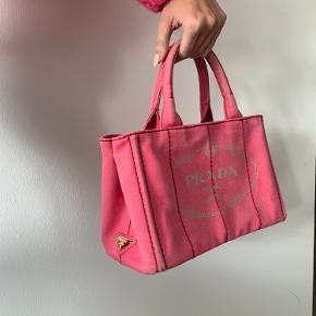 """Smuk og unik Prada taske sælges. Kan gøre ethvert outfit unikt og farverigt! Rummelig håndtaske, med det perfekte look. Sælges i Prada butikkerne for 6500kr, sælges her for 1300.  Modellen hedder """"Prada pink canvas bag"""".  Der er lidt slid i hjørnerne af tasken (almindelige brugsapor når den står), og lidt småslid hist og her.  Skriv til mig for mere information eller flere billeder 😊"""