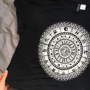 Sort t-shirt med hvidt stjernetegns-print fra H&M Divided. Brugt men stadig i fin stand med ingen brugstegn. Folk der passer størrelser mindre end Medium kan også sagtens passe den.  - Str. M - Pris: 29 kr. - Køber betaler fragt - Kommer fra ikke-ryger hjem