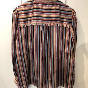 Så fin skjortebluse i forskelligfarvet strib i satinvævet kvalitet med flæser. Skjorten er størrelsessvarende.  Aldrig brugt, kun vasket.  BYTTER IKKE!