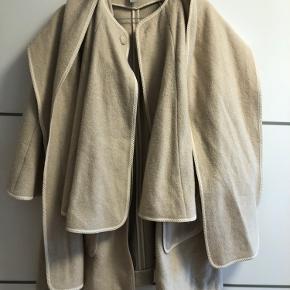 """Super varm jakke i 67 % uld.  Flere lags og med """" vest"""" inde under. Lidt poncho ligende effekt og med indbygget tørklæde om man vil .  Passer en str M også. Har jeg gået med og er jeg selv en str M, trods mærket til en XS"""