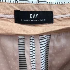 Klassiske sort og hvid stribede bukser fra DAY størrelse 38. Lommer for og bag. Sygningen er gået op lidt op på begge bukseben. Se billede.