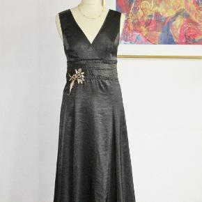 Størrelse: M/L Feminin kjole i sort satin og med guldbroderi under brystet. Kjolen er med foer. Materialet er polyester.  Brystvidde: 45-52 cm x 2 Vidde under brystet: 40 cm x 2 Hoftevidde: 60 cm x 2 Længde: 120 cm  Ingen byt, og prisen er fast