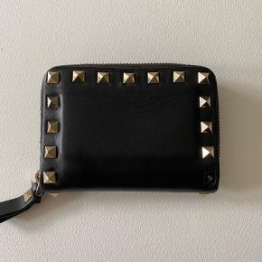 """Valentino Rockstud pung i sort.  Størrelse: 11,5 x 9 x 2,5 cm (BxHxD)  Pungen er brugt og en af """"rockstuds"""" er faldet af på bagsiden ellers egentligt fin stand (se fotos).  Kommer med æske"""
