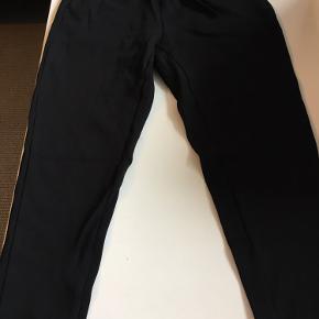 Lækre sorte bukser i kraftig kvalitet med justerbar elastik i taljen og lommer. Rigtig pæn stand. Afh i 6710