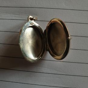 Sølvmedaljon med blomstermønster på begge sider i sølv.
