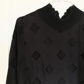 Flot sort skjorte fra h&m med høj hals og mønster i skjorten. Som ny. Knappes i nakken.