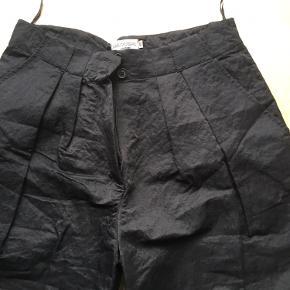 Cargobuks med lommer på lår. I let skinnende polyester. Livvidde er 88 cm
